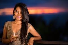 Красивая женщина над предпосылкой захода солнца стоковые фото
