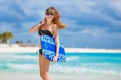 Красивая женщина на пляже с доской для плавать Стоковые Фото
