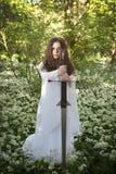 Красивая женщина нося длинное белое платье держа шпагу стоковая фотография