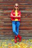 Красивая женщина нося красную куртку и резиновые ботинки в осени вводят в моду около желтых листьев Стоковая Фотография RF
