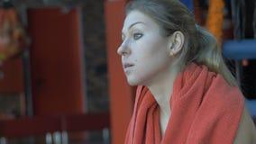 Красивая женщина обтирая ее шею с полотенцем после разминки на спортзале акции видеоматериалы