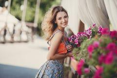 Красивая женщина около вазы с цветками Стоковые Изображения