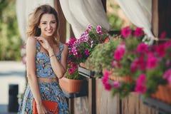 Красивая женщина около вазы с цветками Стоковые Изображения RF