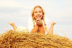 Красивая женщина около стога сена стоковые изображения