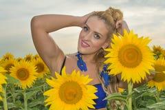 Красивая женщина окруженная солнцецветами Стоковые Изображения