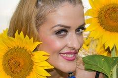 Красивая женщина окруженная солнцецветами Стоковое фото RF