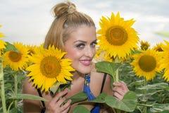 Красивая женщина окруженная солнцецветами Стоковые Изображения RF