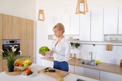 Красивая женщина домохозяйки держа зеленые лист и усмехаться салата Стоковое Изображение
