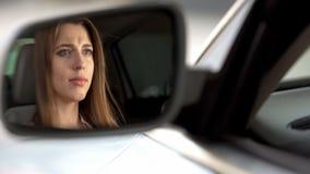 Красивая женщина осадки сидя в автомобиле и плача, прекращает и тоскливость стоковое фото rf