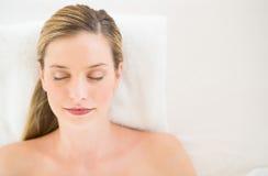 Красивая женщина ослабляя на таблице массажа на курорте здоровья стоковые фотографии rf