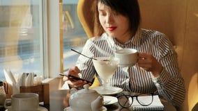 Красивая женщина отдыхая во время обеда, сидя в кафе обед вопроса кофейной чашки дела сподручный раскрыл сверх движение медленное сток-видео