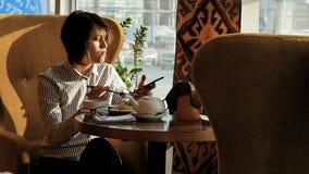 Красивая женщина отдыхая во время обеда, сидя в кафе обед вопроса кофейной чашки дела сподручный раскрыл сверх движение медленное акции видеоматериалы