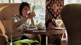 Красивая женщина отдыхая во время обеда, сидя в кафе обед вопроса кофейной чашки дела сподручный раскрыл сверх движение медленное видеоматериал