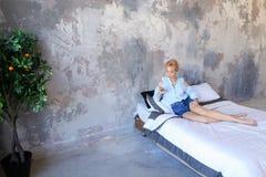 Красивая женщина отдыхая и говоря на телефоне, лежа на двойнике Стоковая Фотография