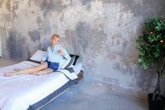 Красивая женщина отдыхая и говоря на телефоне, лежа на двойнике Стоковое Изображение