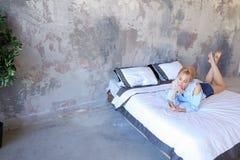 Красивая женщина отдыхая и говоря на телефоне, лежа на двойнике Стоковое Фото