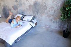Красивая женщина отдыхая и говоря на телефоне, лежа на двойнике Стоковые Изображения