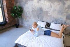 Красивая женщина отдыхая и говоря на телефоне, лежа на двойнике Стоковые Изображения RF