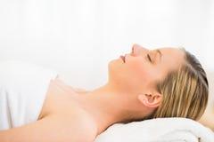 Красивая женщина отдыхая на таблице массажа в курорте здоровья стоковые изображения rf