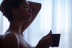 Красивая женщина отдыхая около окна Стоковое фото RF