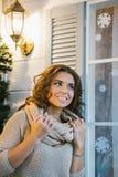 Красивая женщина одела в стойках свитера рядом с окном Стоковое Изображение