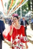 Красивая женщина одела в традиционных костюмах и говорить мобильным телефоном на ` s апреле Севильи справедливо стоковые изображения