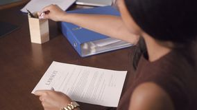 Красивая женщина пишет и подписывает тяжбу на офисе юриста видеоматериал