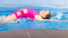 Красивая женщина плавая в бассейне стоковое изображение rf