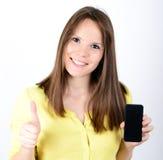 Красивая женщина показывая умный телефон при большой палец руки вверх изолированный дальше Стоковое Изображение