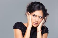 Красивая женщина покрывая ее уши Стоковая Фотография