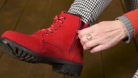 Красивая женщина получает ее красные ботинки и закрывает молнию на темной деревянной предпосылке сток-видео
