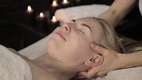 Красивая женщина получая лицевой массаж в курорте лицевая забота кожи в салоне красоты сток-видео