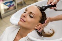 Красивая женщина получая мытье волос в парикмахерской стоковое фото rf