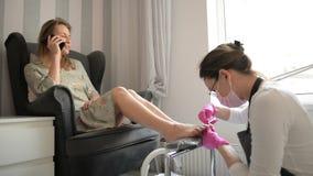 Красивая женщина получая профессиональный Pedicure в салоне красоты спа Мастер очищает ее ногти Клиент говорит дальше видеоматериал