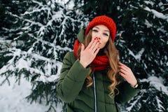 Красивая женщина посылает поцелуй в камере в лесе зимы снежном Стоковое Изображение