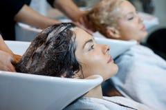 Красивая женщина получая мытье волос в парикмахерской стоковые фото