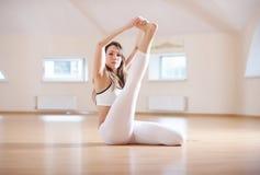 Красивая женщина практикует asana усаженное йогой Kraunchasana в студии йоги Стоковое фото RF