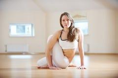 Красивая женщина практикует asana Ardha Matsyendrasana йоги - половинное хребтовое представление извива в студию йоги Стоковое фото RF