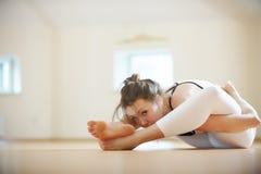 Красивая женщина практикует asana Supta Kurmasana йоги - полное представление черепахи в студию йоги Стоковое Изображение RF