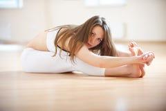 Красивая женщина практикует paschimottanasana asana йоги - усаженный передний загиб в студии йоги Стоковое Изображение RF