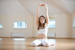 Красивая женщина практикует virasana asana йоги - представление героя в студию йоги Стоковое фото RF