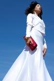Красивая женщина представляя в элегантном белом платье атласа Стоковая Фотография