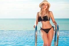 Красивая женщина пригонки в черном костюме и шляпе заплыва представляя на пляже каникула территории лета katya krasnodar стоковые фотографии rf