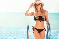 Красивая женщина пригонки в черном костюме и шляпе заплыва представляя на пляже каникула территории лета katya krasnodar стоковые изображения