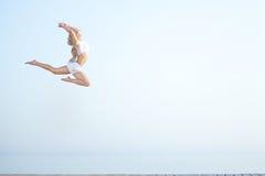 Красивая женщина пригонки скача на пляж близко Стоковые Изображения