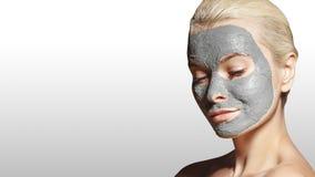 Красивая женщина прикладывая белую лицевую маску Косметики Девушка спа прикладывает маску глины лицевую на серой предпосылке стоковое изображение