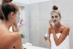Красивая женщина прикладывая маску к ее стороне стоковое изображение