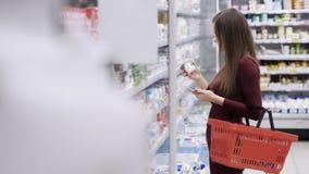 Красивая женщина принимает продукты от холодильника и кладет ее в красную корзину на супермаркете видеоматериал