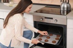 Красивая женщина принимая вне поднос испеченных печений от ovenк стоковое фото