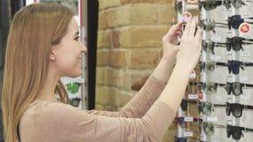 Красивая женщина принимая фото солнечных очков на дисплее на магазин видеоматериал